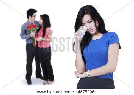 Betrayal concept. Sad woman crying in front of young couple standing on the back isolated on white background