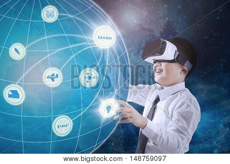 Image of little boy wearing virtual reality glasses and touching virtual screen with globe