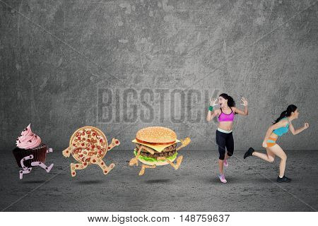 Two sporty woman running away from junk food while wearing sportswear