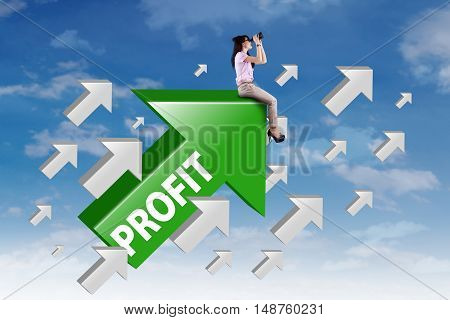 Female worker sitting on the upward arrow with profit word while looking at the sky through binocular