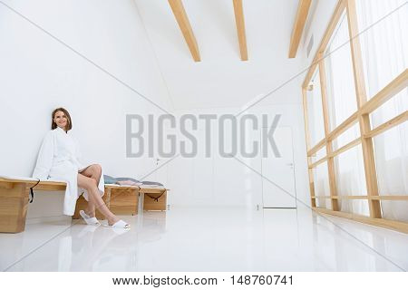 Never felt more pampered. Beautiful young woman relaxing in spa, sitting on wooden bench and smiling