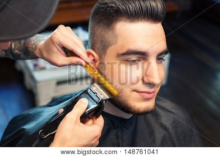 Young man having beard shaven