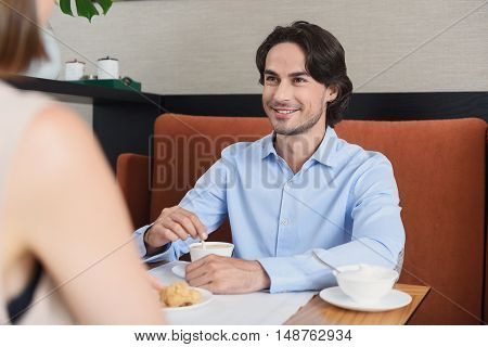 Amazing coffee and relaxing atmosphere. Handsome man holding cup of coffee and looking at his girlfriend with smile