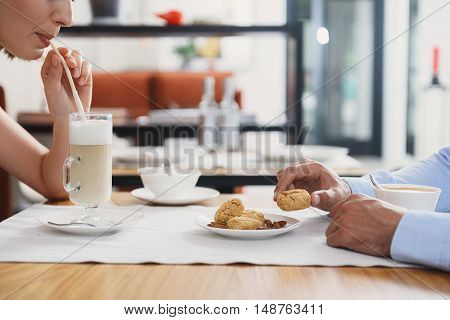 Day starts after coffee. Cropped shot of woman drinking latte and man holding cookies in his hand and drinking coffee