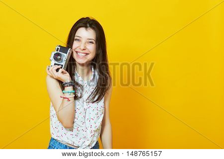 Happy hipster girl with retro camera in studio against yellow background with copy space