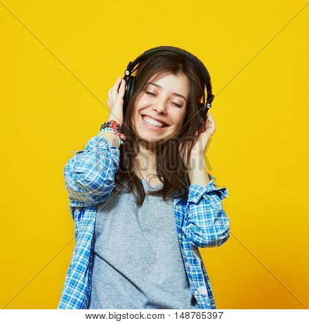 Young woman with headphones listening to music. Teenager girl enjoying music against isolated over yellow background