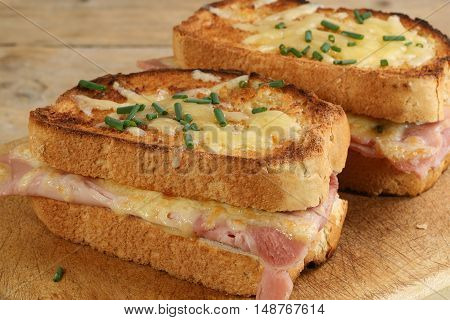 two slices of croque monsieur cheese and ham on a wooden board
