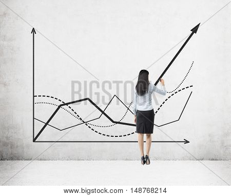 Rear view of businesswoman in skirt drawing a growing graph on concrete wall. Concept of statistician's work