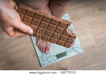 Overweight Woman Standing On Scale And Holding Chocolate