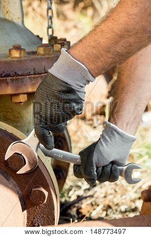 Hands with Work Gloves Holding a Wrench and Tighten very Rusty Bolts