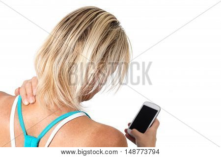 Middle age woman is holding her sore neck by left hand. In the right hand is holding a smart phone. All is isolated on the white background. All potential trademarks are removed.