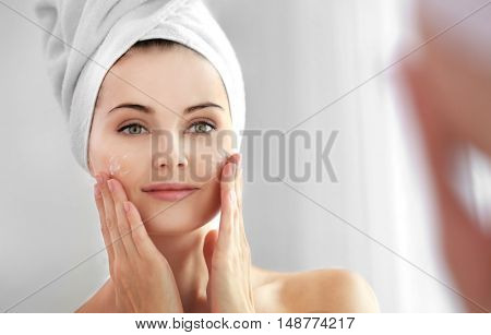 Mirror reflection of beautiful young woman with towel around head applying cream onto face