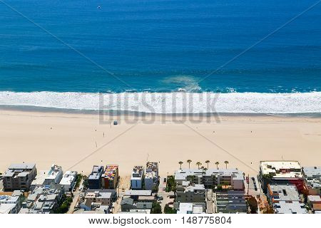 LOS ANGELES, USA - MAY 27, 2015: Part of the beach in Venice with residential buildings facing the beach and the ocean. There are hardly any people on the beach and in the ocean.