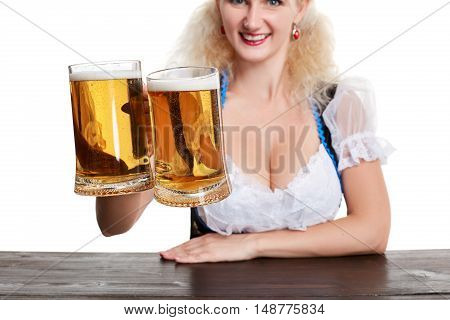 Beautiful young blond girl drinks out of oktoberfest beer stein. Isolated on white background. sits by the table. Close up