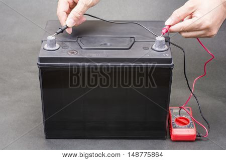 Black car battery which measure voltage with a tester