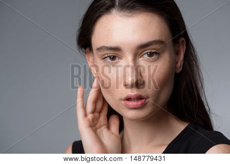 skincare and beauty concept, close up of a beautiful young freckled woman looking into camera with copyspace