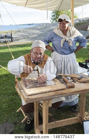 Fairhaven Massachusetts USA - September 24 2016: Member of Fairhaven Village Militia reenacting a Revolutionary War tinsmith working at his craft at the Revolutionary War historical encampment at Fort Phoenix in Fairhaven Massachusetts