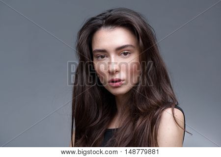 beauty and skincare concept, portrait of a serene young freckled girl looking into camera with copyspace
