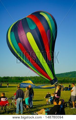 Vertical photo of a hot air balloon being filled while people watch on.