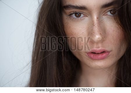 beauty and skin care concept, face of a serene pretty woman on light grey background
