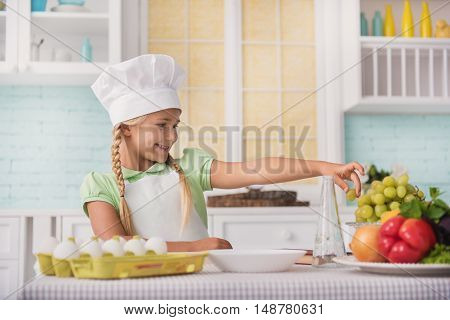 Pretty girl is having fun in kitchen and smiling. She is standing near table and taking grape with appetite. Kid is wearing chef hat and apron