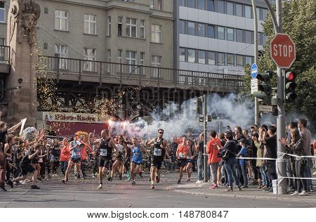 BERLIN GERMANY - SEPTEMBER 25 2016: Spectator With A Torch And Runners At Berlin Marathon 2016