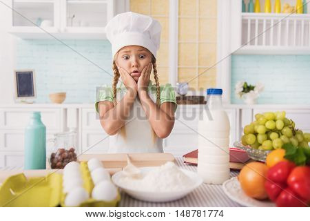 Puzzled girl does not know how to cook. She is looking at flour with shock and touching her head. Child is standing in apron in kitchen