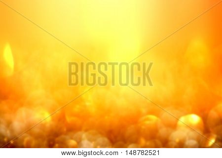 Golden glitter Christmas abstract background with defocused sparkle lights over dark gold shining backdrop