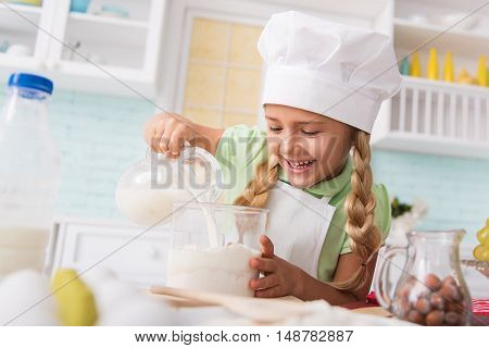 Joyful girl is making dough with pleasure and smiling. She is pouring milk into bowl