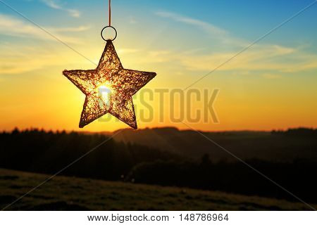 Landscape, sunny dawn in a field.Bright christmas star and sunset. Christmas background.