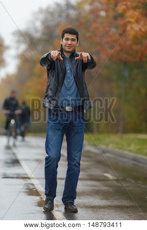 Young handsome man in black jacket posing on background of alley in city park