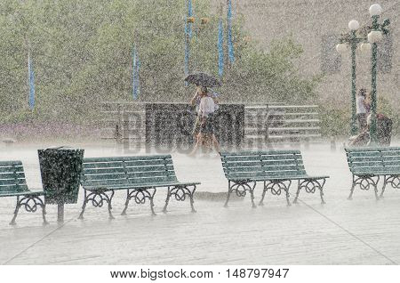 Quebec City, Canada - July 27, 2014: Couple walking in heavy rain with umbrella on boardwalk street close to Chateau Frontenac.