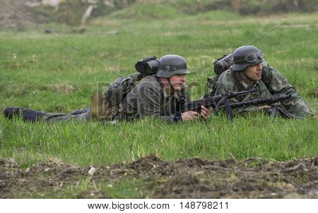 SAINT PETERSBURG, RUSSIA - MAY 05, 2015: German infantryman and machine gunner lay down in the grass. Reconstruction of the episode of the great Patriotic war