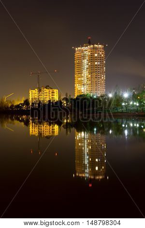 Night scene with new buildings in downtown of Donetsk with reflection in the calm river water. Green park, new building construction, cranes, dark gray sky.