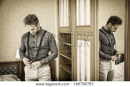 Sexy handsome man standing in his bedroom, dressing with shirt and suspenders, next to wooden wardrobe door