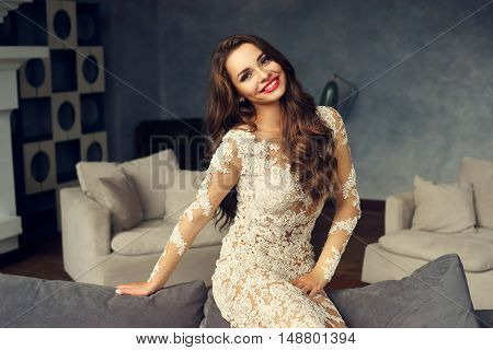 Young stylish sexy girl in white lace evening dress sitting on gray couch in simple lounge interior. Happy smiling woman with longcurly hair looking at you