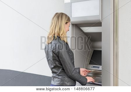 Young Woman Withdrawing Money At An Atm