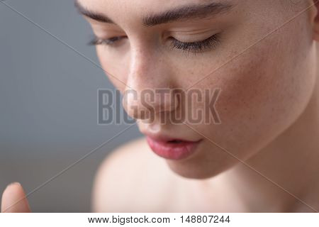 skin care concept, close up of a young freckled woman