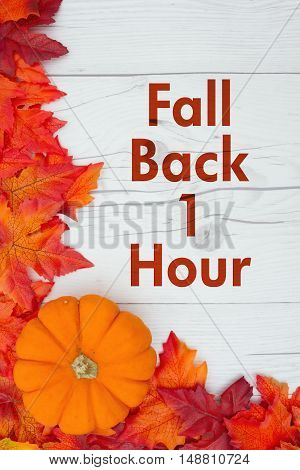 Fall Time Change Some fall leaves and a pumpkin on weathered wood with text Fall Back 1 Hour
