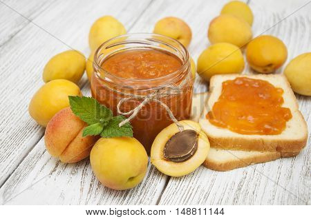 Fresh apricot jam in a jar with mintwith sandwiches and apricot fruits on wooden table