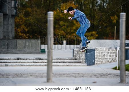 Boy doing skateboard trick smithgrind on ledge