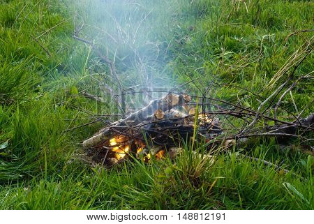 Bonfire. Green grass. Halt in hike. Smoke of the bonfire.