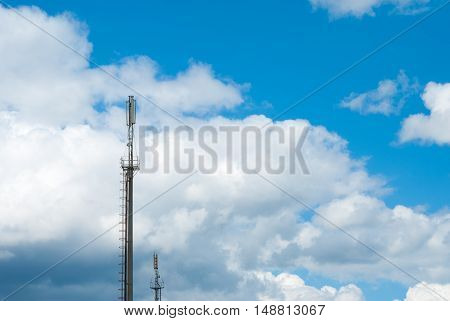 Mobile communications tower on the sky background. Large clouds. Aerials of cellular communication. GSM Tower. Covering mobile.