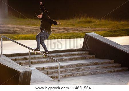 Boy doing skateboard trick tailslide in skatepark