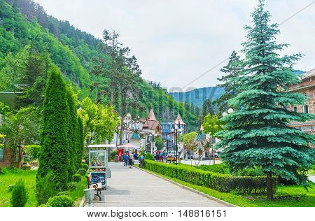 BORJOMI GEORGIA - MAY 26 2016: The central street of resort with lush coniferous trees and scenic mansions on May 26 in Borjomi.