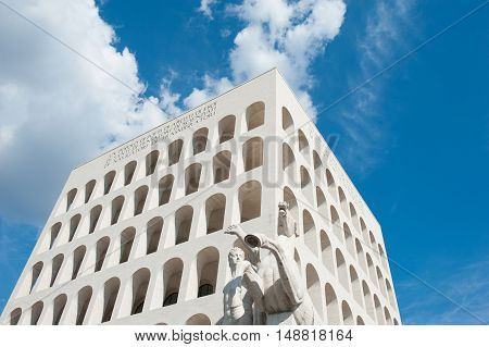 Palazzo della civilta italiana view from the ground in sunny day with blue cloudy scenic sky Rome modern architecture landmark poster