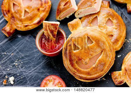 Halloween pizza idea - homemade calzone shaped pumpkin with ham and cherry tomatoes sauce