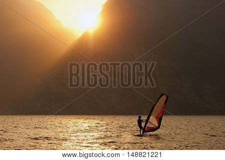 Young man surfing the wind during sunset