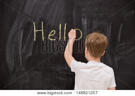 Back view on cute kid boy writing Hello word with chalk on the backboard in school class. Education elementary school learning back to school concept. schoolboy writing on chalk board in classroom.