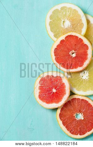 Top view on cut red and yellow grapefruit on turquoise wooden background. Juicy and fresh fruit. Healthy eating concept.